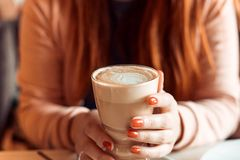Woman with red nails sitting and holding a hot cup of coffee. Closeup of hands with latte, Red manicure royalty free stock photography