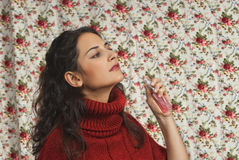 Woman in red over floral background. Woman with parfume with colorful floral background Royalty Free Stock Images