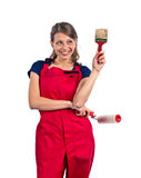 Woman in red overalls with painting tools Stock Images