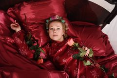 Woman in red pajamas lying on a bed on silk red linen with hair curlers and a rose in her hand royalty free stock photos