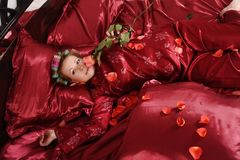 Woman in red pajamas lying on a bed on silk red linen with hair curlers and a rose in her hand stock photo