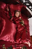 Woman in red pajamas lying on a bed on silk red linen with hair curlers and a rose in her hand stock photography