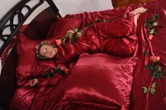 Woman in red pajamas lying on a bed on silk red linen with hair curlers and a rose in her hand royalty free stock image