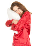 Woman in red pajamas with white pillow Stock Images
