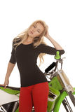 Woman red pants green motorcycle close lean elbow Stock Photo