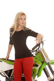 Woman red pants green motorcycle stand front close serious Royalty Free Stock Photo