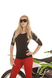 A woman in red pants and sun glasses in front of motorcycle Royalty Free Stock Images