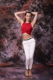 Woman in red pants and a white top posing on marble colored background. Fashion photo. Sensual portrait of a thin girl. Beautiful woman in red pants and a white Stock Photos