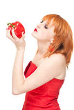 Woman with red pepper. Portrait of young attractive redhead in red dress holding fresh red pepper, isolated on white background Royalty Free Stock Image