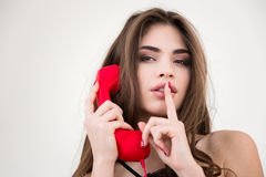 Woman with red phone tube showing finger over lips Royalty Free Stock Image