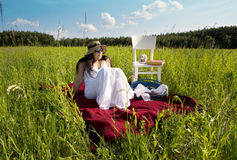 Woman on Red Picnic Blanket. Woman on Red Picnic Cloth on Meadow with Picnic Basket Stock Photo