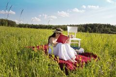 Woman on Red Picnic Blanket. Woman with Hat in White Dress is Sitting on Red Cloth on Green Meadow with White Chair and Picnic Basket and Reading a Book Stock Images