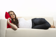 Woman with red pillow in bed Stock Photos