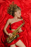 Woman in red playing the saxophone Stock Images