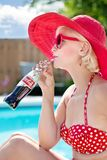 Woman in Red Polka Dot Print Bikini Wearing Red Frame Sunglasses Drinking Coca Cola Beverage in Blue and White Clouds Royalty Free Stock Photography