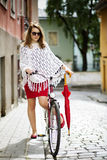 Woman in red put leg on bicycle Stock Images