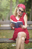 Woman in red reading and telephoning Stock Photo