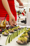 Woman in red ress take appetiser from table. Fresh tartar gourmet snack royalty free stock photo