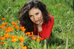 Woman in red resting on green grass, outdoors portrait Royalty Free Stock Photo