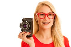 Woman in red with a retro camera isolated over white background stock photo