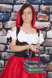 Woman red riding hood basket look scared. A woman in her red riding hood out fit holding a basket with a serious expression on her face stock images