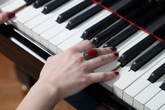 A woman with red ring playing piano Stock Images