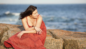 Woman in red on rocky beach at sunset 4. A beautiful woman in a red dress sits on a large rock at a beach during sunset Royalty Free Stock Image