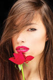 Woman and red rose. Pretty woman and red rose near her lips Stock Photo