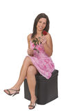 Woman with a red rose. Sitting on a chair Royalty Free Stock Photography