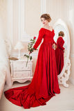 Woman in red with rose. Woman dressed in red dress standing near mirror Royalty Free Stock Image