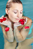 Woman with red rose petals in pool Royalty Free Stock Photos