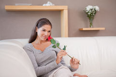 Woman with a red rose sitting on the couch Stock Photo