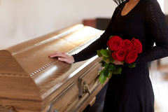 Woman with red roses and coffin at funeral Royalty Free Stock Photo