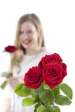 Woman with red roses.GN. Young woman standing with a rose in her hand and a bouquet with roses in the foreground.GN stock images