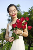 Woman with red roses in the park Royalty Free Stock Image