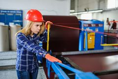 Woman in red safety helmet at metal tile roof manufacturing fact. Portret of nice beautiful woman in red safety helmet at metal tile roof manufacturing factory royalty free stock photos