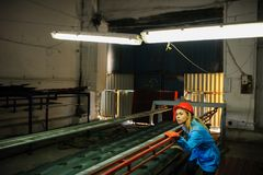 Woman in red safety helmet at metal tile roof manufacturing fact Stock Photo