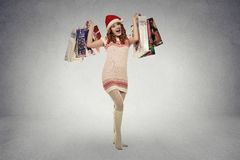 Woman in red santa claus hat with christmas gifts, shopping bags Royalty Free Stock Image