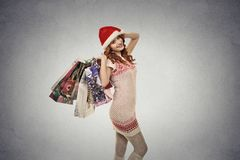 Woman in red santa claus hat with christmas gifts, shopping bags Stock Images