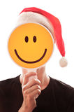 Woman with a red Santa Claus hat. Hiding her face behind a smiley sign Stock Image