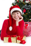 Woman in red Santa hat lying under Christmas tree with gifts Royalty Free Stock Image