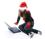 woman in red Santa hat working on laptop Stock Photos