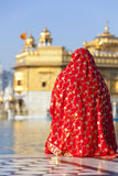 Woman in red sari at Golden Temple. Stock Photos