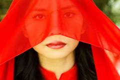 Woman with red scarf covering her face Stock Images