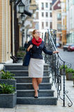 Woman in a red scarf down the stairs to the street Stock Photos
