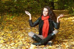 Woman in red scarf sits cross-legged and raising his hands Royalty Free Stock Photography