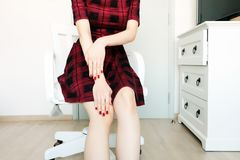 Woman in Red Scot Dress and Red Nails Manicure. A Beautiful Woman Standing on Wooden in White Room Studio Background. Red Nails Manicure. Beautiful Woman in Red Royalty Free Stock Photos