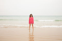 Woman in red at seashore Stock Photos