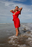 Woman in red in shallow beakers under blue sky stock photo