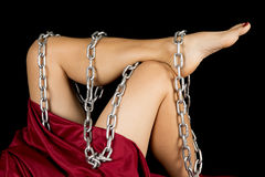 Woman in red sheet legs out chain on them close Royalty Free Stock Image